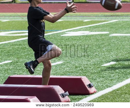 A Young Boy Is Running Sideways Over Red Barriers While Catching A Football During A Summer Camp Wor