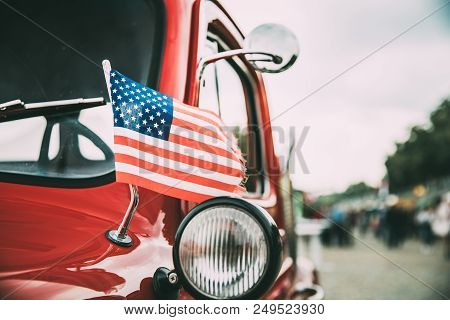 Close Side View Of Red Pickup Truck With Small American Flag Waving.