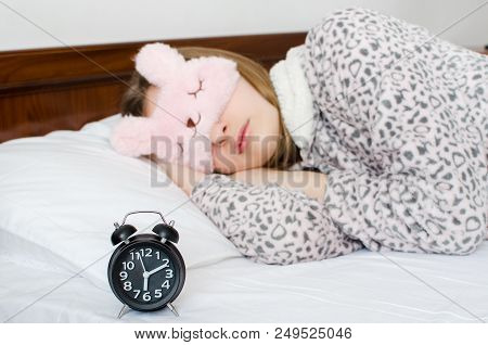 Young Woman Girl In Cute Sleep Mask And Warm Pajamas Sleep With Alarm Clock On The Bed In The Mornin