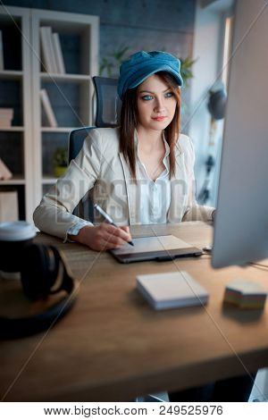 Creative young modern woman is devoted to her career and working late on computer at office