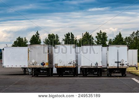 Semi Tractor Trailers Parked In A Row With Doors Closed Under A Blue Cloudy Sky With Trees