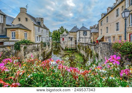 A Picturesque Village On The Banks Of The River Aure In Bayeux France