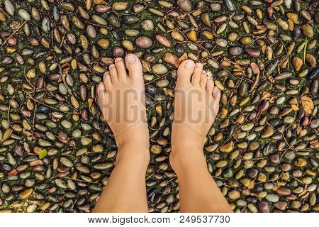 Woman Walking On A Textured Cobble Pavement, Reflexology. Pebble stones on the pavement for foot reflexology. poster