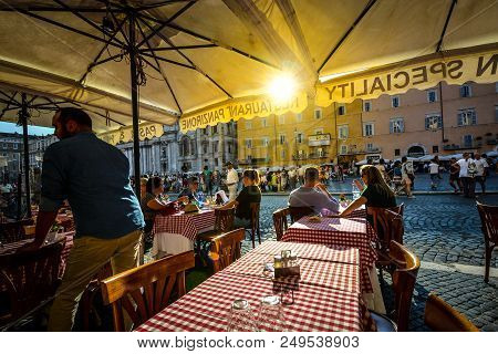 Rome, Italy - September 16 2016: A Couple Dining Out In A Romantic Italian Restaurant As The Sun Goe