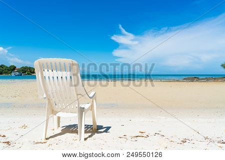 Empty Beach Chair Over Looking The Clear Blue Sky And Ocean