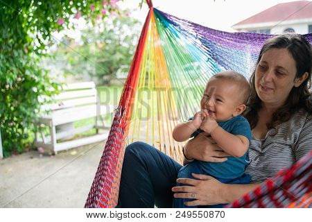 The Little Boy And Mother Are Sitting At The Hammock, Both Are Happy