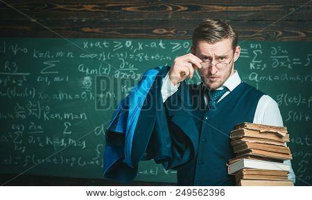 Check Homework. Teacher Formal Wear And Glasses Looks Smart, Chalkboard Background. Teacher Finished