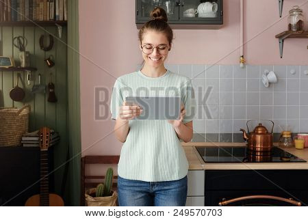 Closeup Photo Of Young Attractive European Lady Pictured In Her Kitchen With Tablet Pc In Hands Look