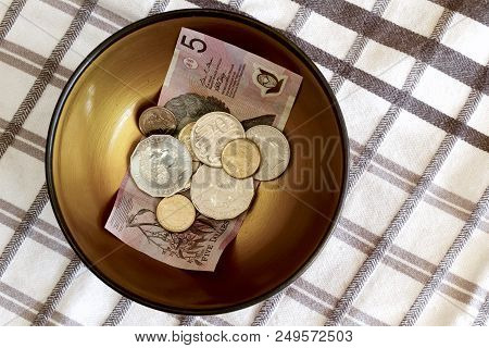 Australian Notes And Coins As Tips In A Bowl At A Restaurant.