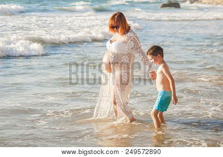Beautiful Young And Pregnant Caucasian Woman Walking With Her Son On A Seaside Holding Him By His Ha
