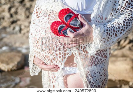 Young Pregnant Caucasian Woman Holding Tiny Baby Girl Shoes In Her Hands And Holding Her Belly. Expe