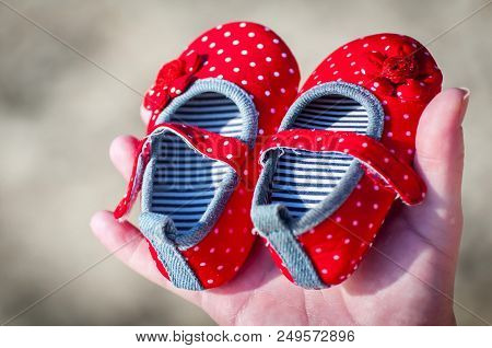 Young Pregnant Woman About To Become Mother Holding Tiny Red Baby Girl Shoes. Expecting A Girl Daugh