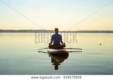 Man Practicing Yoga On A Sup Board During Sunny Morning On A Large River. Stand Up Paddle Boarding -