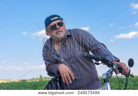 Outdoor Portrait Of A Bearded, Chubby Senior Man Getting Ready To Summer Ride On A Bicycle