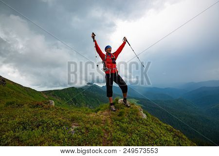 Joyful Adventurer Is Standing On The Cliff With Open Arms On The Background Of Low Heavy Clouds Floa