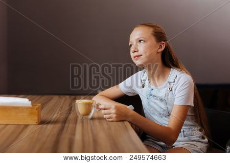 Blonde-haired Teenager. Blonde-haired Teenager Wearing White Shirt Drinking Decaf Latte While Sittin
