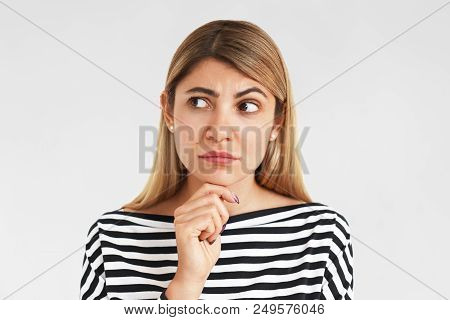 Horizontal Shot Of Attractive Stylish Girl In Striped Top Keeping Hand On Her Chin And Looking Sidew