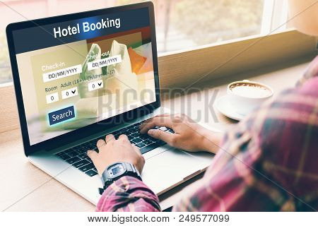 Man Using Laptop To Make Hotel Booking Reservation In Cafe Restaurant.