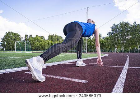 Girl At Start Of Running Track. Running On Cross. Sports Start. Girl In Pose On The Starting Line Of