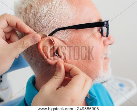 Patient Is Assisted In Setting Up The Hearing Aid. Treatment Of Hearing Of Elderly People Using A He