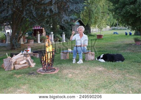 Die Attraktive Frau Isst Am Lagerfeuer Gebratene Spiegeleier, Ihr Hund Schaut Zu