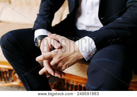 Man Sitting With His Hands Crossed. Men's Hand In A Blue Suit, Watch On The Man's Hand, The Hand Of