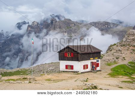 Mountain Hut With High Rocky Ridge In Clouds On Background. Tre Cime Di Lavaredo National Park, Dolo