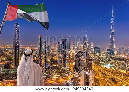 Arabian Man Watching Night Cityscape Of Dubai With Modern Futuristic Architecture In United Arab Emi