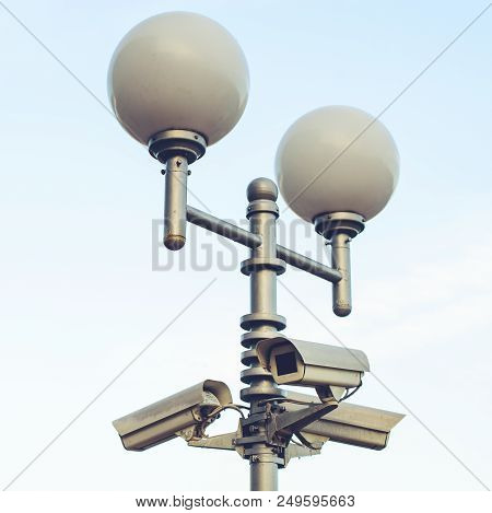 Public City Video Surveillance Cameras And Street Lamps On The Lamppost Over Sky, Toned Image