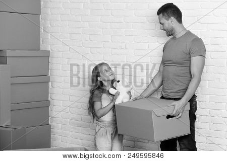 New Home And Family Concept. Daughter And Father Hold Box, White Teddy Bear And Unpack Or Pack. Girl