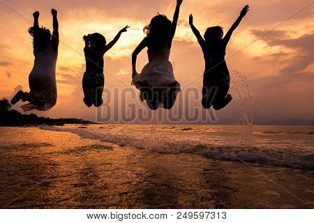 Summer Silhouette Of Asian Girls Gang Are Jumping In Sea On The Beach. Vacation On Weekend Concept.