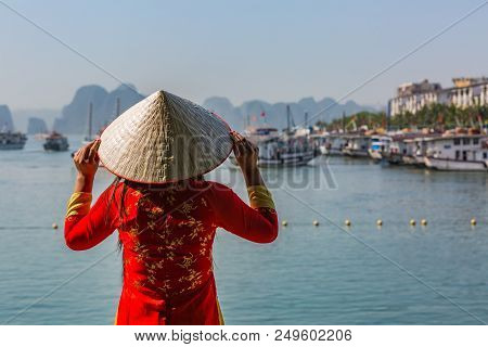 Attractive Woman In Vietnamese National Costume Traveling By Boat In Ha Long Bay, Vietnam. Travel To