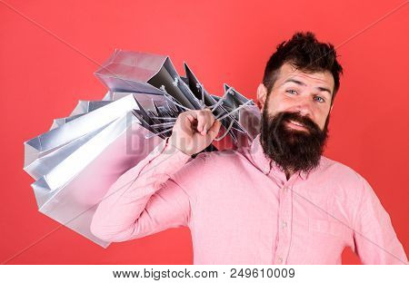 Man With Beard And Mustache Carries Shopping Bags On Shoulder, Red Background. Guy Shopping On Sales