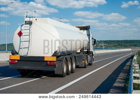fuel truck rides on highway, white blank cistern for oil, rear view, one object on road