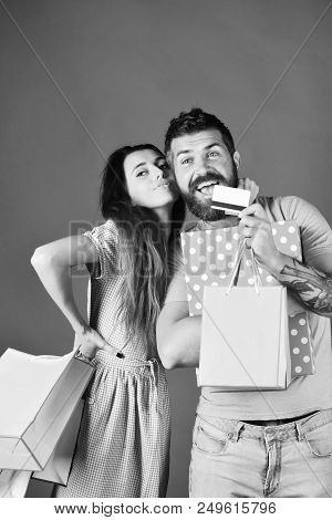 Guy With Beard And Girl With Happy Faces Do Shopping. Couple In Love Holds Shopping Bags On Green Ba
