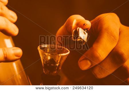 bong and a lighter in his hands. A man smokes cannabis weed, a Smoke on a black background. Concepts of medical marijuana use and legalization of the cannabis. On a black background poster