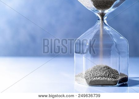 Sliver Sand Running Through The Shape Of Modern Hourglass On White Table.time Passing And Running Ou