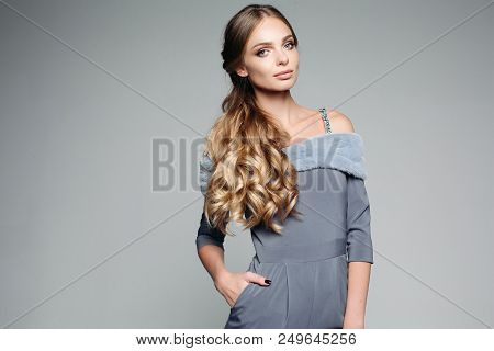 Gorgeous Blondie Woman Wearing In Gray Outfit Holding Hand In Pocket, Seriously Looking At Camera. S