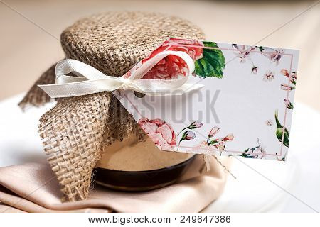 Gift Jam Decorated With A Ribbon And A Sackcloth As A Present For Guests Standing At A Wedding Party