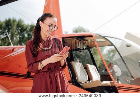On My Way. Low Angle Of Cheerful Vigorous Woman Posing Near Helicopter And Holding Phone