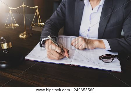 Advice And Justice Concept. Justice Scales And Justice Hammer And Female Lawyer Use Pen, Working Leg