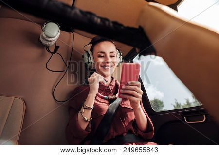 Good News. Low Angle Of Jovial Energetic Woman Sitting In Helicopter And Reading Message