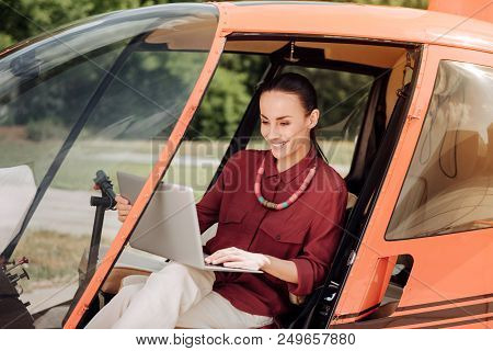 At Helicopter. Enthusiastic Jovial Woman Using Laptop And Sitting In Helicopter