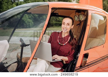 Inside Helicopter. Joyful Jovial Woman Carrying Laptop And Sitting In Helicopter