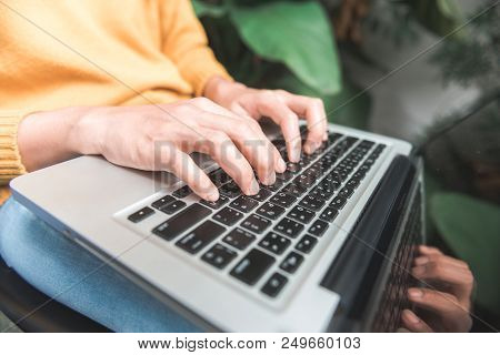 Close Up Young Woman Shopping Online With Her Laptop In A Coffee Shop Garden With A Background Of A