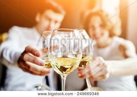 Leisure, Celebration, Drinks, People And Holidays Concept - Happy Couple And Friend Clinking Glasses