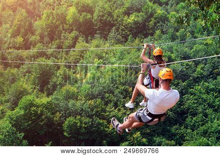 Zipline Is An Exciting Adventure Activity. Man And Woman Hanging On A Rope-way. Tourists Ride On The