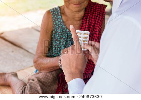 The Doctor Is Explaining How To Take The Medicine To The Patient.