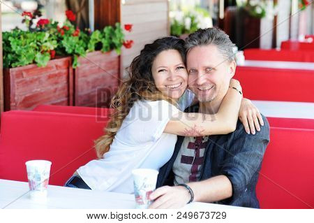 Smiling in love couple sitting in a street cafe, outdoors