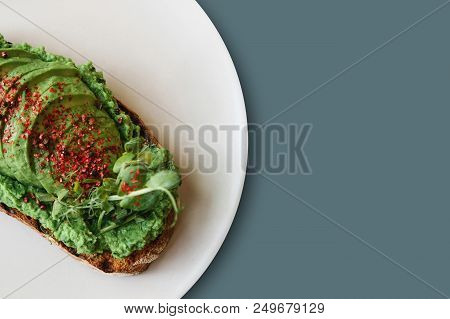 Delicious and nutritious veggie toast or sandwich with avocado and guacamole in a minimal style. Healthy food. A useful snack. Nearby place for text. poster